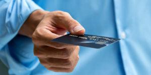 24906746 closeup of hand holding and giving credit card for payment